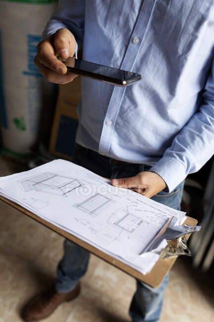 Architect taking smartphone picture of construction plan — Stock Photo