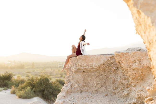Mujer joven despreocupada sentada con los brazos extendidos en el acantilado en el campo - foto de stock
