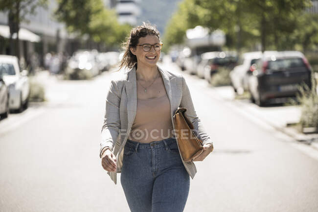 Smiling young woman with bag walking on road during sunny day — Stock Photo