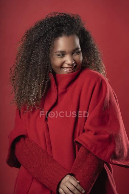 Улыбающаяся молодая женщина в теплой одежде смотрит в сторону, стоя на красном фоне — стоковое фото