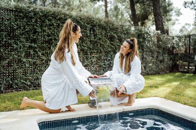 Gemelle allegre in ginocchio vicino alla fontana a bordo piscina nella località turistica — Foto stock