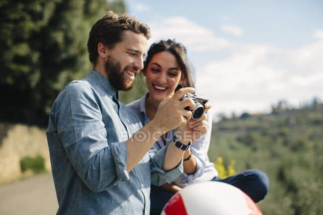 Primo piano di felice coppia alla ricerca di immagini in macchina fotografica — Foto stock