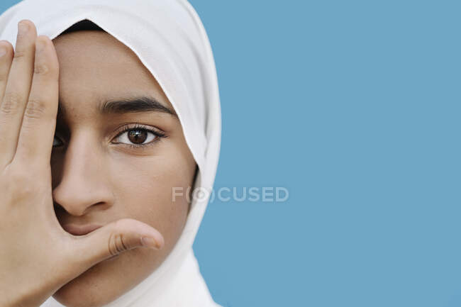Muslim girl covering eye with hand against blue background — Stock Photo