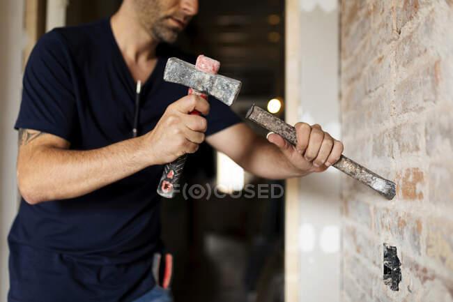 Будівельник за допомогою молотка і палички на цегляній стіні. — стокове фото