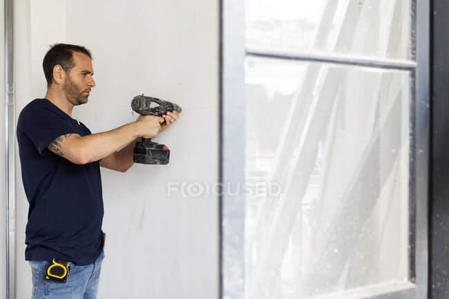 Працівник будівництва за допомогою свердла біля стіни. — стокове фото