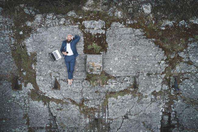 Vista aérea do empresário vestindo terno ouvir música enquanto deitado em terra na floresta — Fotografia de Stock