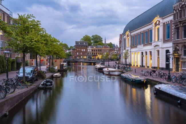 Países Bajos, Holanda Meridional, Leiden, Barcos amarrados a lo largo del canal de la ciudad del Rin al atardecer - foto de stock