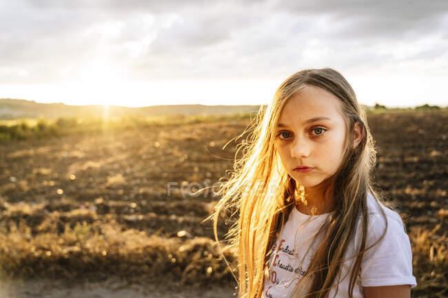 Милая девушка с длинными светлыми волосами, стоящая на фоне неба на закате — стоковое фото