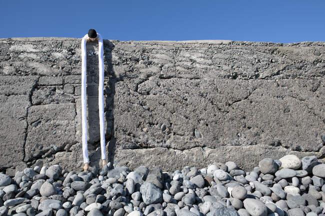 Woman with artificial long hands bending over retaining wall at beach — Fotografia de Stock