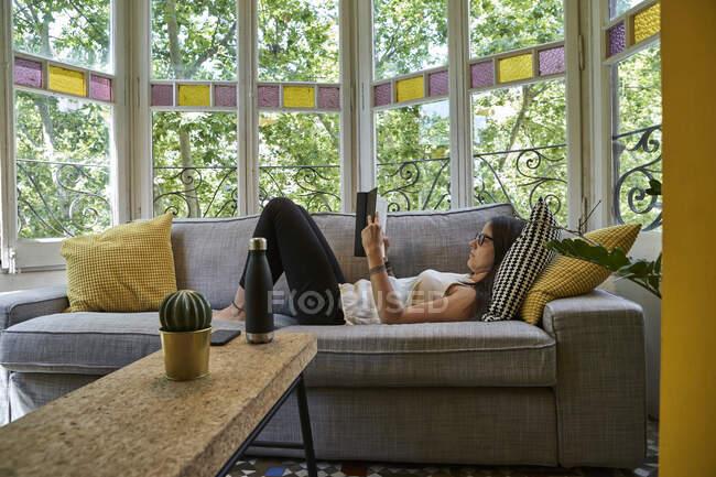 Женщина читает книгу, расслабляясь на диване в гостиной — стоковое фото