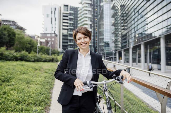 Посмішка жінка - професіонал з велосипедом, що стоїть на стежці міста. — стокове фото