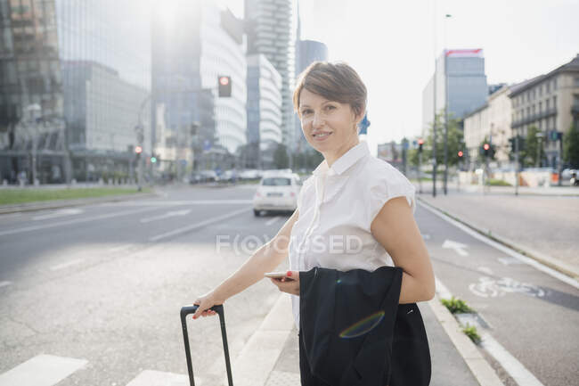 Smiling female professional holding mobile phone and suitcase while standing on road in city — Fotografia de Stock