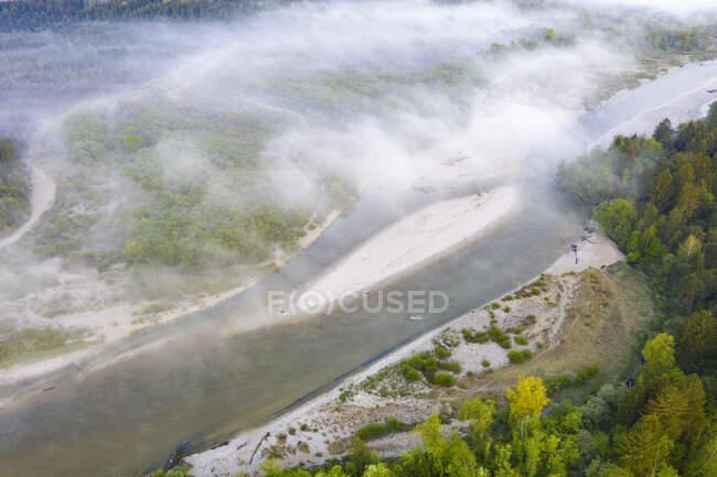 Німеччина, Баварія, вид ранкового туману, що пливе над берегом річки Ізар. — стокове фото