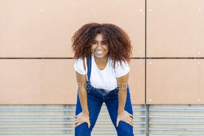 Mujer joven sonriente con el pelo afro de pie contra la pared en la ciudad - foto de stock