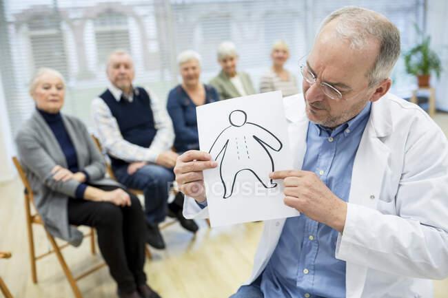 Grupo de personas mayores que asisten al asesoramiento de salud en un asilo de ancianos - foto de stock