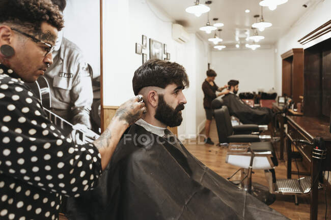 Trendy barber styling client's hair at salon — Stock Photo