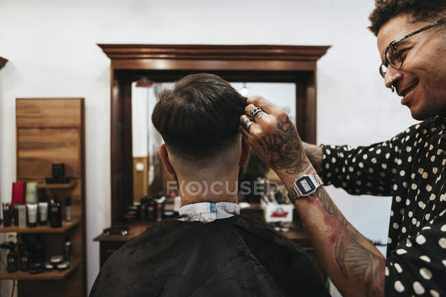 Feliz peluquero cortando el pelo del cliente en el salón - foto de stock
