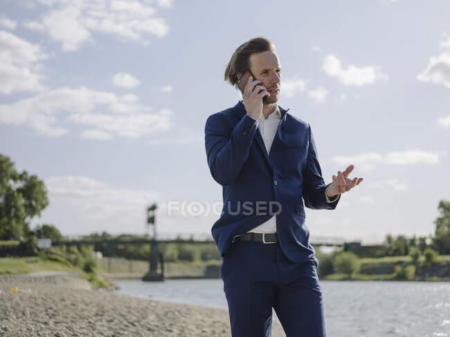 Empreendedor do sexo masculino falando por telefone inteligente, enquanto em pé na margem do rio contra o céu — Fotografia de Stock