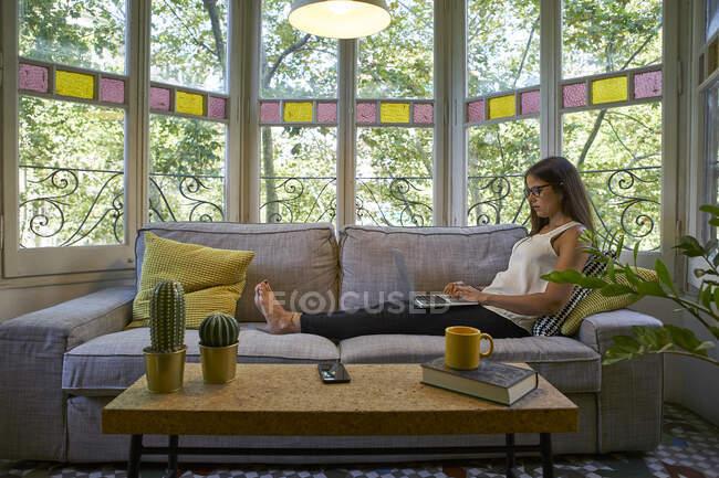 Donna che lavora sul computer portatile mentre è seduta sul divano a casa — Foto stock