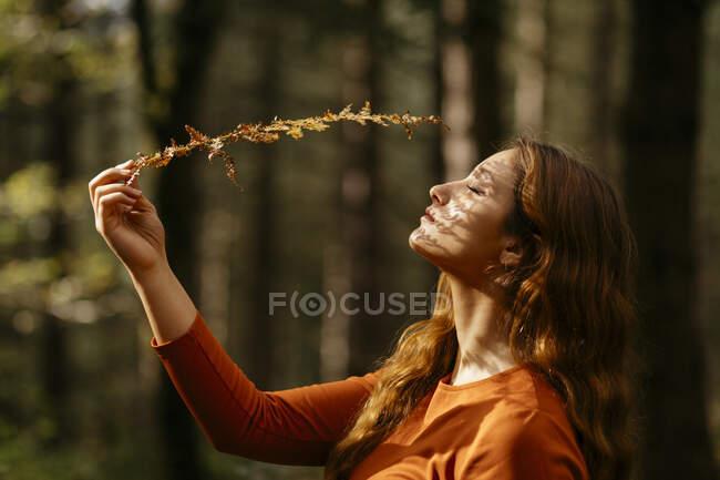 Primo piano di bella donna con gli occhi chiusi azienda impianto nella foresta — Foto stock