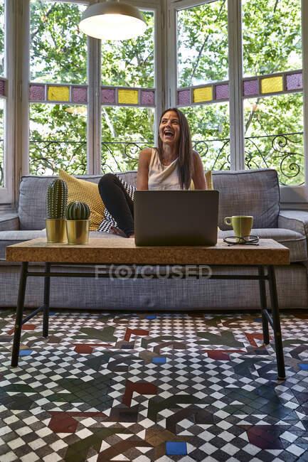 Весела жінка сидить перед ноутбуком на дивані. — стокове фото