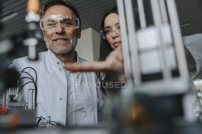 Close-up of scientists with protective eyewear examining machine in laboratory — Stock Photo