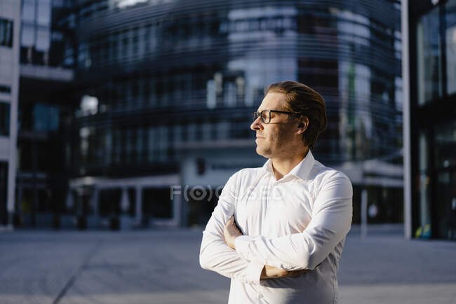 Businessman with closed eyes in sunshine in the city — Stock Photo