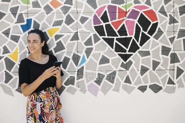 Retrato usando teléfono inteligente frente a la pared colorida - foto de stock