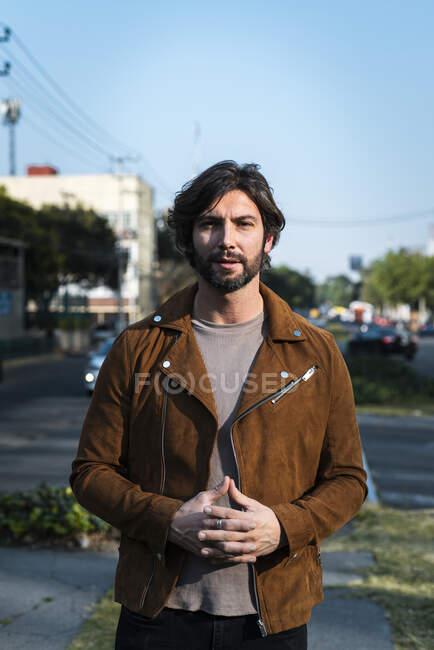 Hombre guapo con chaqueta de pie en la calle contra el cielo despejado en la ciudad - foto de stock