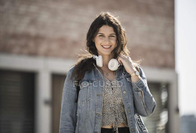 Mujer joven sonriente con auriculares en la ciudad en un día soleado - foto de stock