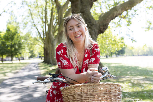 Happy woman leaning on bicycle at public park — Stock Photo