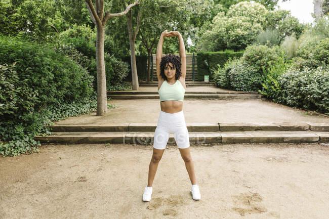 Атлетичная молодая женщина, вытягивающая руки в парке — стоковое фото