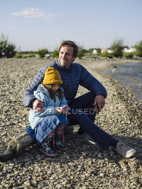 Sonriente padre con hija sentada en el tronco en la orilla del río contra el cielo durante el día soleado - foto de stock