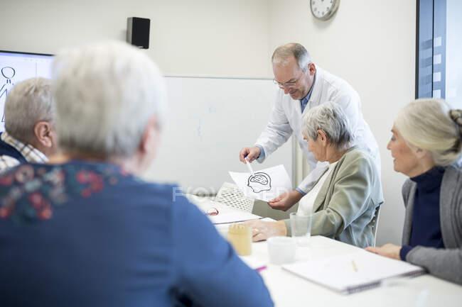 Врач, объясняющий функции мозга группе пожилых людей — стоковое фото