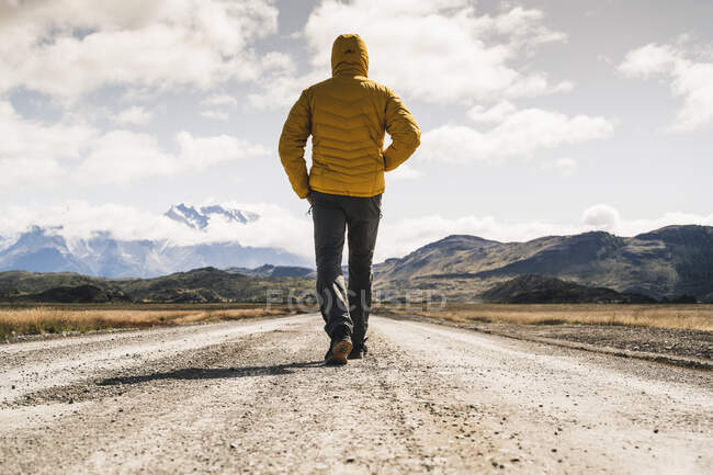 Male hiker walking on dirt road against sky at Torres Del Paine National Park, Patagonia, Chile — Stock Photo