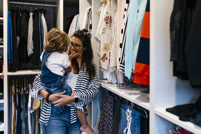 Mãe feliz carregando filha enquanto em pé por armários em camarim em casa — Fotografia de Stock