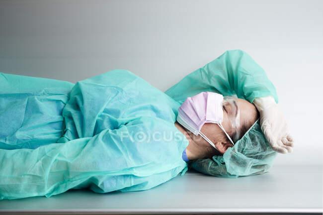 Стомлена жінка - лікар у захисному робочому одязі, що відпочиває на лавці в лікарні. — стокове фото