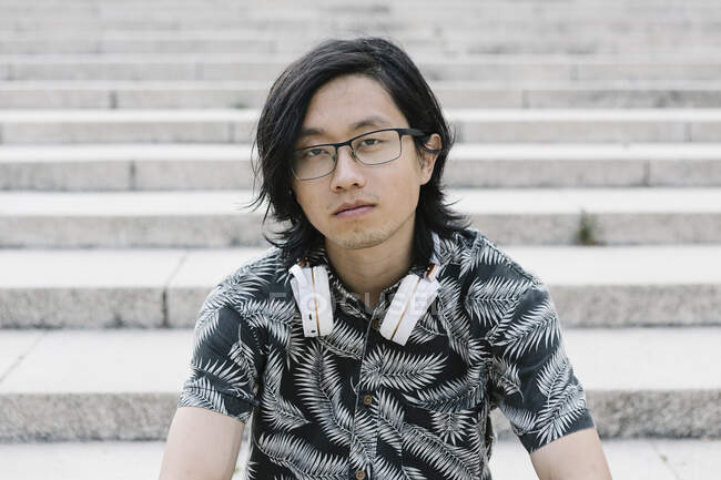 Close-up of young man wearing eyeglasses with headphones sitting on steps in city — Stock Photo