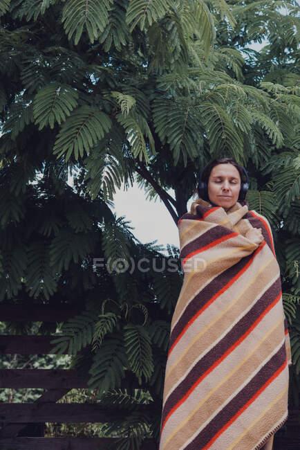 Mujer con los ojos cerrados envuelta en manta escuchando música a través de auriculares por árbol acacia dealbata - foto de stock