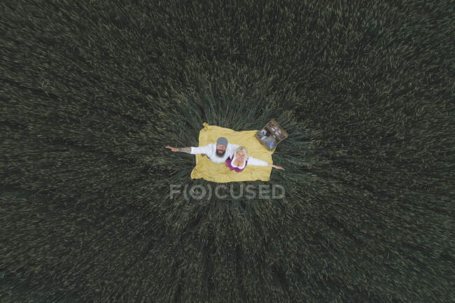 Aerial view of couple with arms outstretched standing on blanket amidst green cornfield - foto de stock
