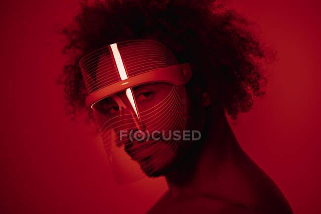 Primer plano del joven con máscara de luz led roja contra la pared en casa - foto de stock