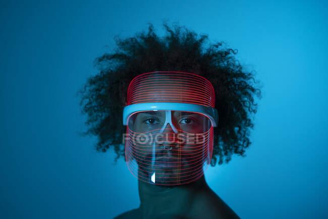 Joven serio con máscara led roja contra la pared en casa - foto de stock