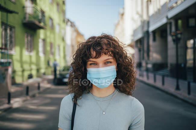 Brunette curly woman wearing protective mask in city — Fotografia de Stock