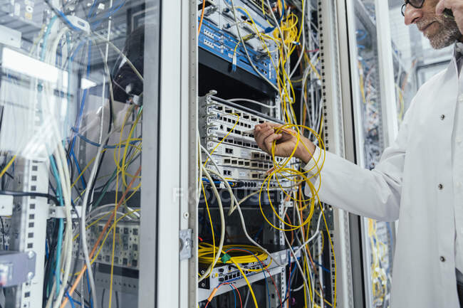 Mature man plugging in transceiver on fiber optic cable in data center — Stock Photo
