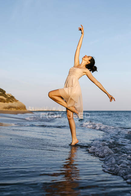 Delicate ballerina dancing on the beach at sunset — стокове фото