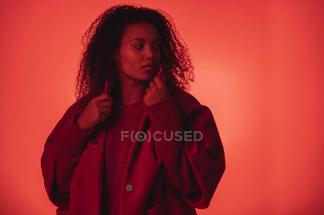 Confident woman wearing red coat looking away while standing against orange background — Stock Photo