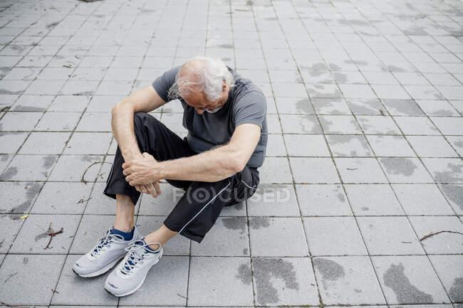 Уставший старший мужчина сидит на тропинке в городе — стоковое фото