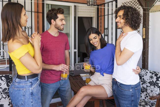 Happy young friends talking at back yard - foto de stock