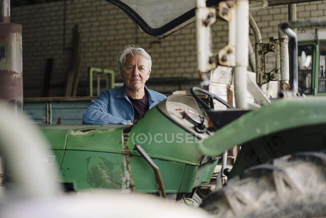 Retrato de um homem idoso em uma fazenda com trator no celeiro — Fotografia de Stock