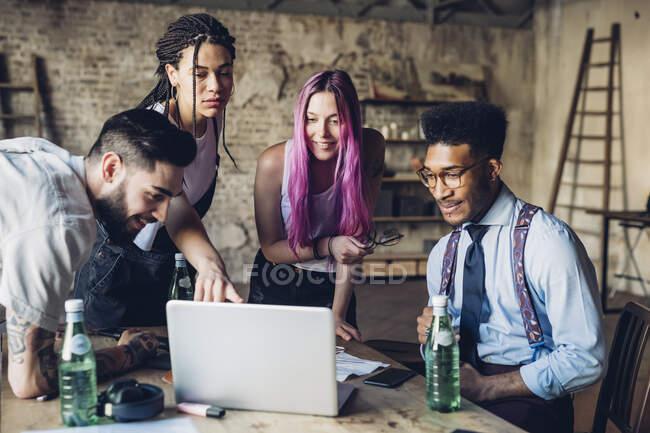 Team creativo che si riunisce in ufficio loft utilizzando il computer portatile — Foto stock
